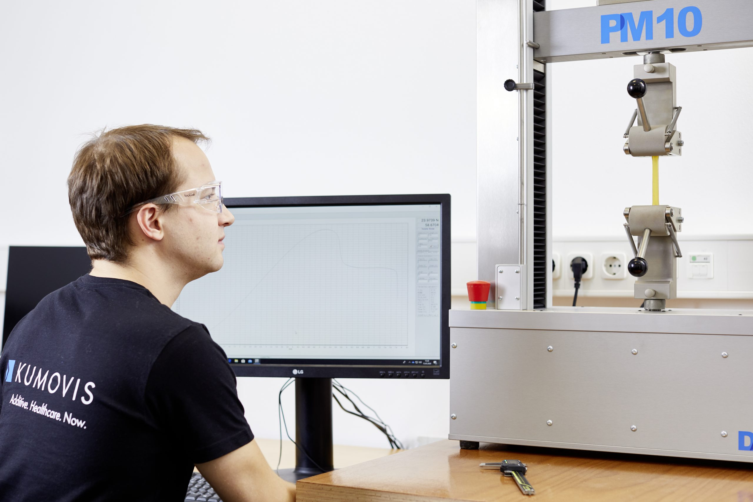 Kumovis employee sitting in front of computer monitor and test machine